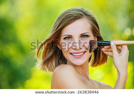 Beautiful young woman close up puts on face powder brush, against green of summer park. - stock photo