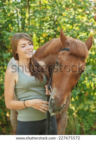 Beautiful young woman close-up with horse, against green of summer park. - stock photo