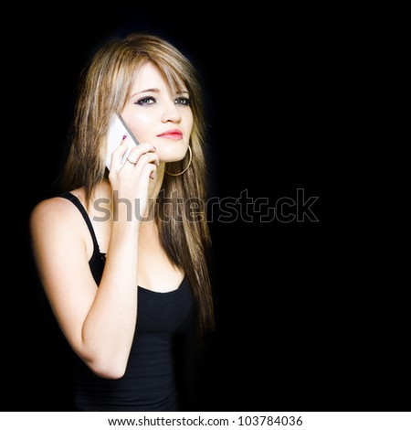Beautiful young woman communicating on cell phone while looking onto black copy space - stock photo