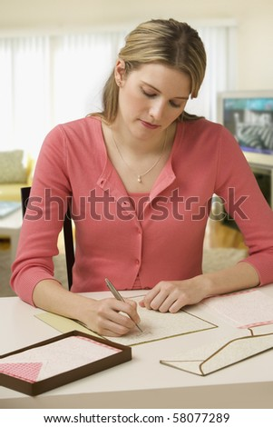 Beautiful young woman concentrates while writing a letter at her desk.  Vertical shot.