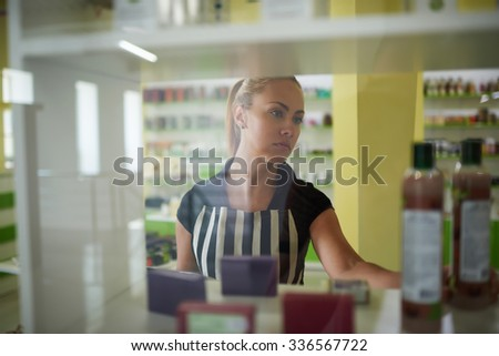 Beautiful young woman consultant lays out beauty on store shelves, attractive female reads the contents of the product before making a purchase in cosmetic shops, buyer consider aromatic fluids - stock photo