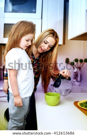 Beautiful young woman cook with a child of five years at the kitchen - stock photo