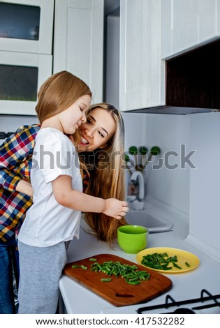 Beautiful young woman cook with a child of five years tasty food at the kitchen - stock photo