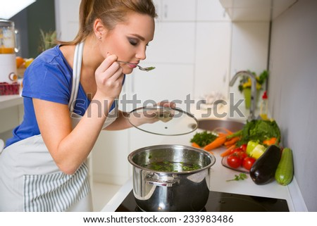 Beautiful young woman cooking and testing the food in the kitchen - stock photo