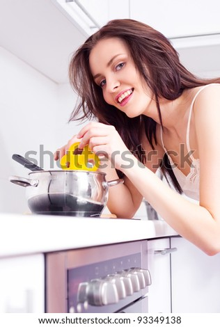 beautiful young woman cooking dinner in the kitchen - stock photo