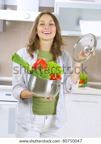 Beautiful Young Woman cooking fresh Vegetables.Dieting Concept.Vegetarian food