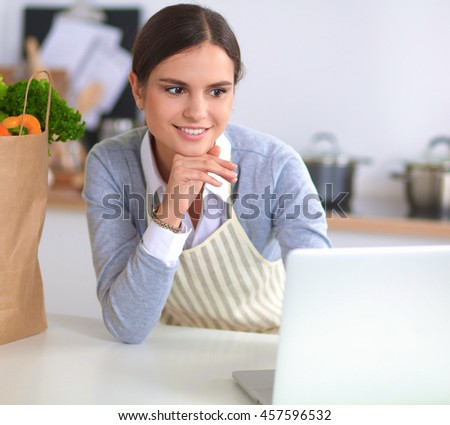 Beautiful young woman cooking looking at laptop screen with receipt in the kitchen