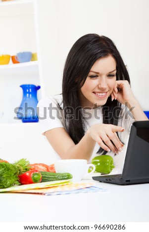 Beautiful young woman cooking looking at laptop screen with receipt in the kitchen, happy smile - stock photo
