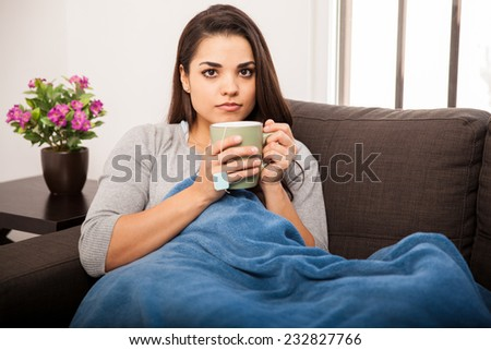 Beautiful young woman covered in a blanket at home and drinking some tea on a cold day
