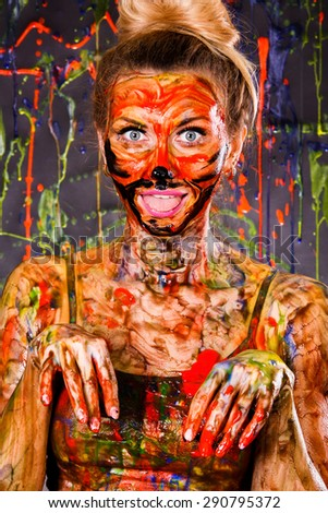Beautiful young woman covered with multicolored paints - stock photo