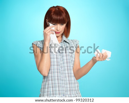 beautiful young woman, crying, wiping her tears with napkins, on blue background