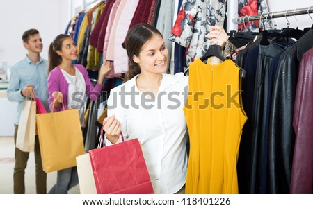 Beautiful young woman customers chooses liked things in the boutique
