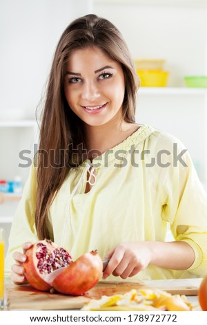 Beautiful young woman cutting pomegranate in the kitchen. Looking at camera.