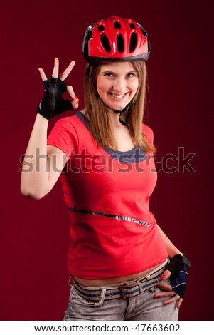 beautiful young woman cyclist in a red shirt and a helmet shows OK - stock photo