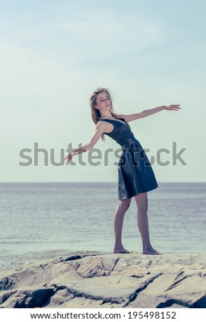 Beautiful young woman dancing outdoors, sunny day