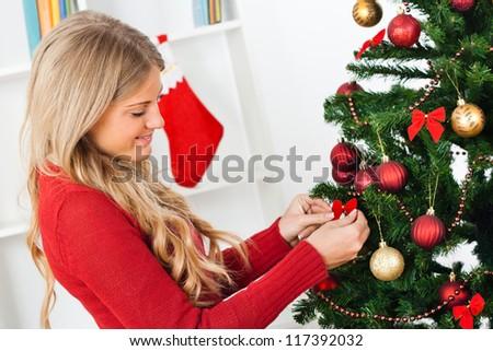 Beautiful young woman decorating Christmas tree,Decorating Christmas tree - stock photo