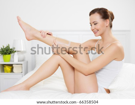 Beautiful young woman depilating skin on legs by waxing is in the bedroom - indoors