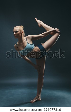 Beautiful young woman do yoga exercise on the dark background - stock photo