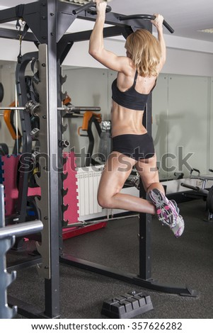 beautiful young woman doing body-building in the Gym - stock photo