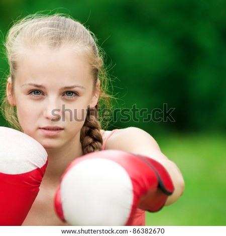 Beautiful young woman doing box exercise in red gloves at green park. Boxer - stock photo