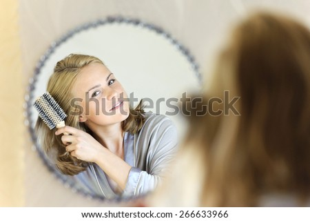 Beautiful young woman doing hair with hairbrush