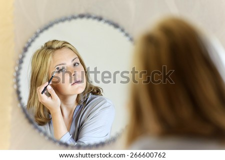 Beautiful young woman doing make-up
