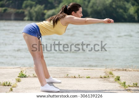 Beautiful young woman doing stretching exercise by the river.