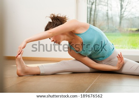 Beautiful young woman doing stretching exercise indoor in front of the window - stock photo
