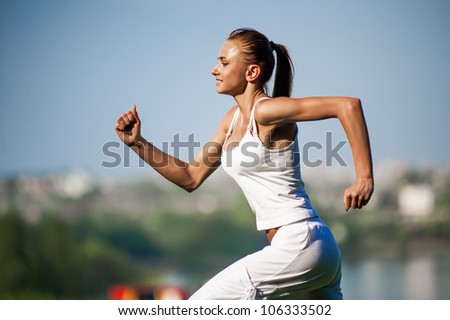 Beautiful young woman doing stretching exercise on green grass at park - stock photo