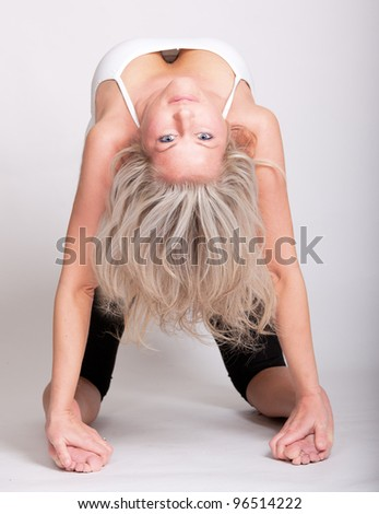 Beautiful young woman doing yoga bridge pose - stock photo