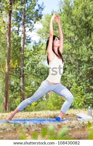 Beautiful young woman doing  yoga exercising on the grass in forest - stock photo