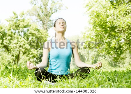 Beautiful young woman doing yoga in the park.