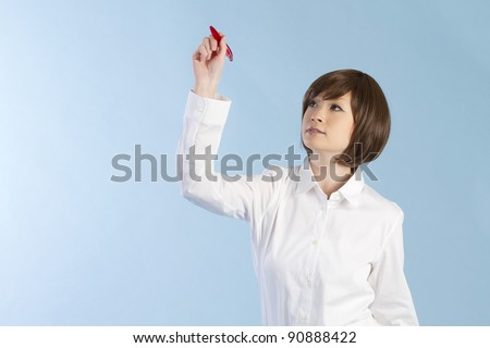 Beautiful young woman drawing on blue background - stock photo