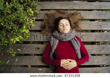 Beautiful young woman dreaming on a wooden bridge - stock photo
