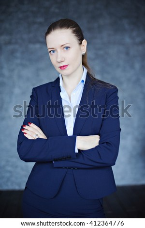 Beautiful young woman dressed in business style, textured background, look at the camera. - stock photo
