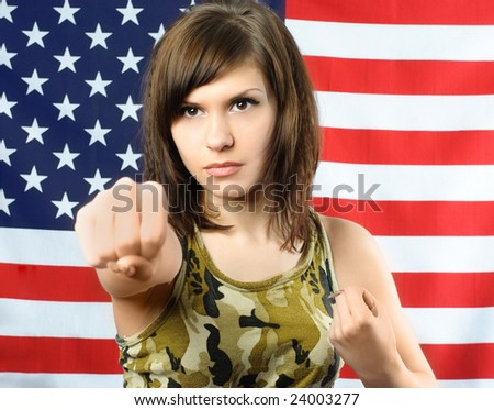 beautiful young woman dressed in camouflage standing opposite an American flag  is ready to fight