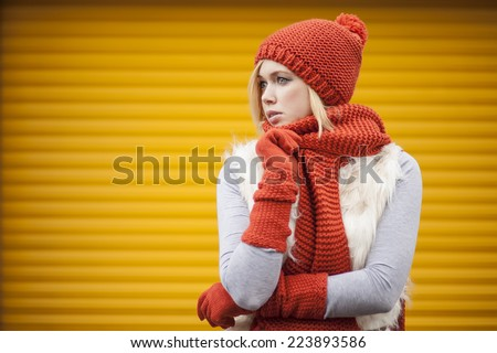 beautiful young woman dressed in colorful autumn clothes against yellow garage gates - stock photo