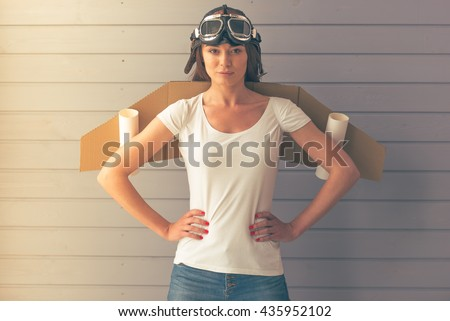 Beautiful young woman dressed like a pilot with toy wings is smiling and looking upward, standing akimbo against gray wall - stock photo