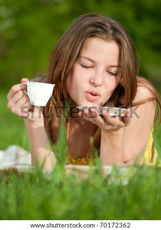 Beautiful young woman drink hot coffee outdoor on green grass
