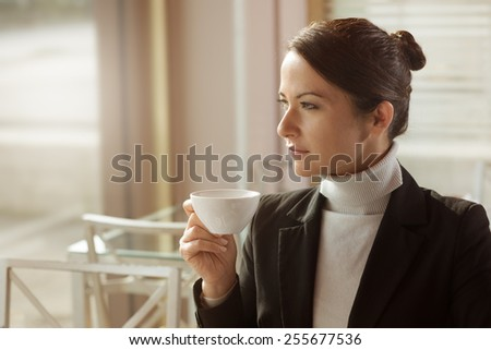 Beautiful young woman drinking a coffee and staring at the window - stock photo