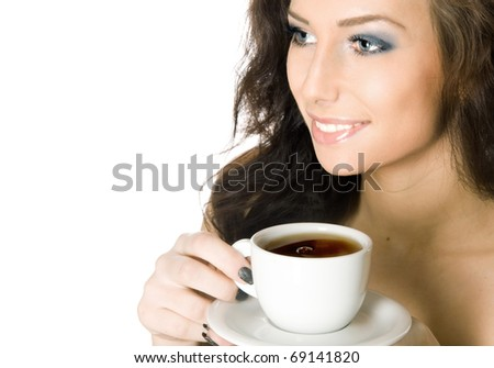 Beautiful young woman drinking a cup of hot tea or coffee - stock photo