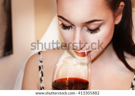 Beautiful young woman drinking a glass of red wine