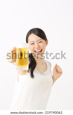 Beautiful young woman drinking beer, isolated on white - stock photo