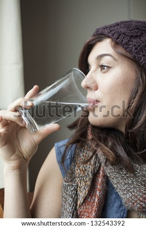 Beautiful young woman drinking glass of water. - stock photo