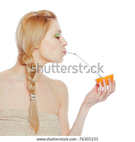 Beautiful young woman drinking juice direct from an orange fruit using a straw - stock photo