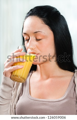 Beautiful young woman drinking orange juice,Healthy refreshment - stock photo
