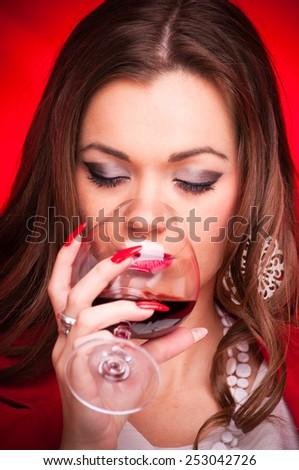 Beautiful young woman drinking red wine - studio shot on red background - stock photo