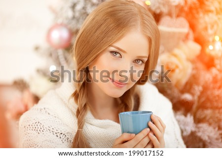 Beautiful young woman drinking tea at the Christmas tree. Beautiful girl celebrates Christmas with a cup of cocoa. - stock photo