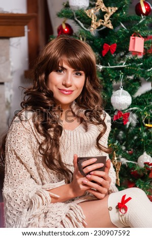 Beautiful young woman drinking tea at the Christmas tree. Beautiful girl celebrates Christmas with a cup of cocoa over living room