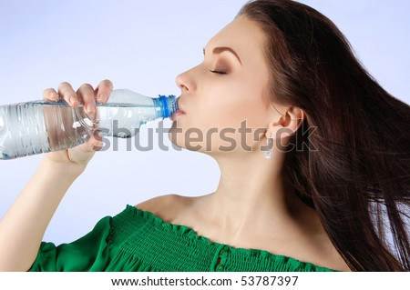 Beautiful young woman drinking water